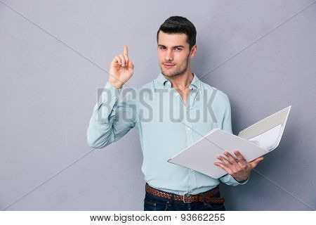 Handsome man holding folder and pointing finger up over gray background. Having idea!