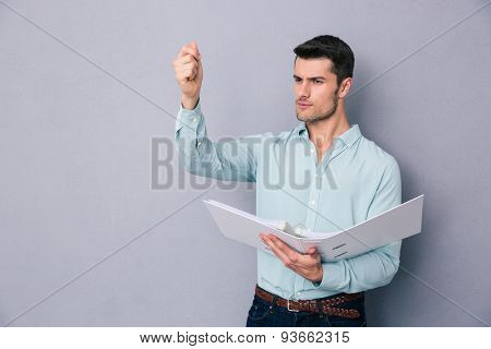 Pensive young man holding folder over gray background and looking away