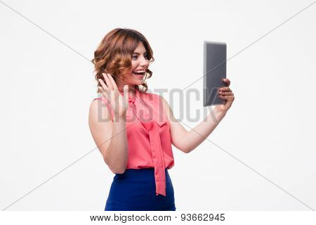 Casual woman making greeting gesture to tablet computer isolated on a white background