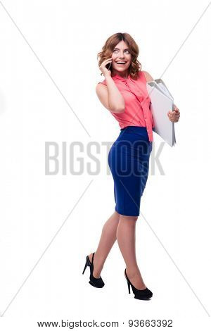 Full length portrait of a happy businesswoman talking on the phone and holding folders isolated on a white background. Looking up