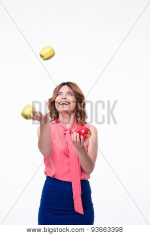 Happy woman juggles with apples isolated on a white background