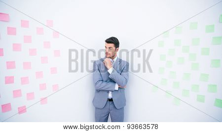 Handsome businessman standing near wall with stickers in office