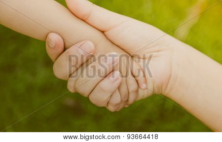 Mother holding baby hand ( Filtered image processed vintage effect. )