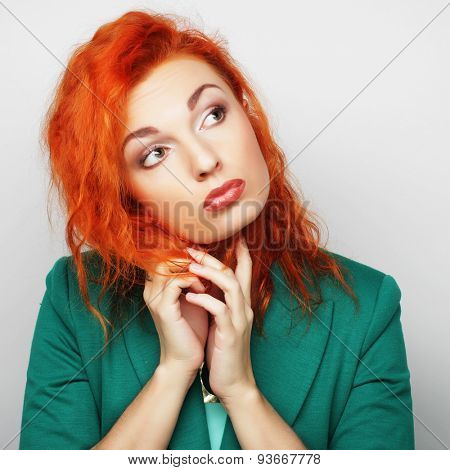 Thinking woman pondering over something, studio shot
