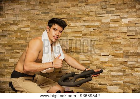 Handsome young man doing spinning on bike