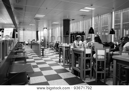 GENEVA, SWITZERLAND - SEPTEMBER 11, 2014: people in airport cafe. Geneva International Airport is the international airport of Geneva, Switzerland. It is located 4 km northwest of the city centre