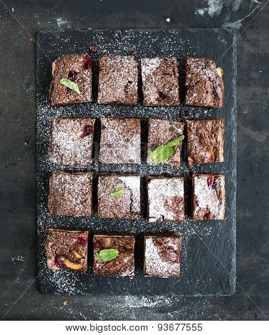 Chocolate and raspberry brownie squares on black stone board over dark grunge backdrop