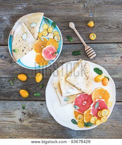 Spring vitamin breakfast set. Thin crepes or pancakes with fresh grapefruit, orange, kumquat, honey,