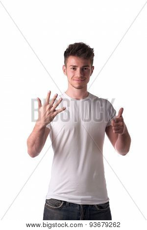 Handsome young man counting to six 6 with fingers and hands