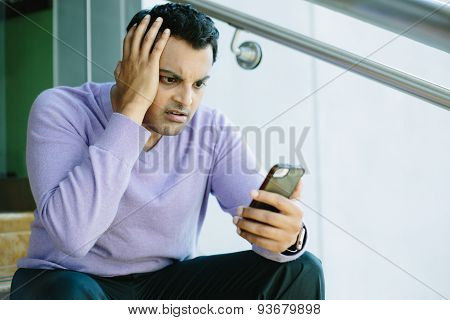 Man Looking At Bad News On Cellphone
