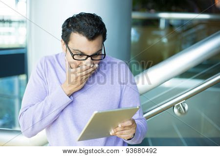 Man Amused By What He Sees On Tablet