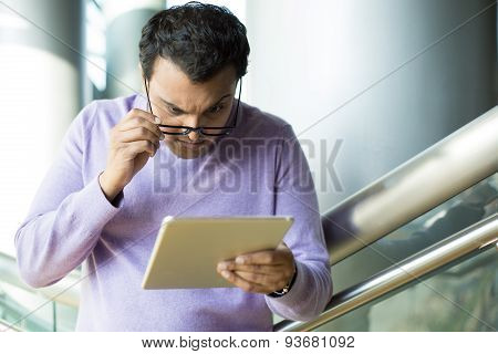 Man Perplexed By What He Sees On Tablet