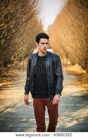Handsome young man walking along rural road
