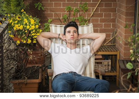 Handsome young man in balcony day-dreaming, sitting on chair