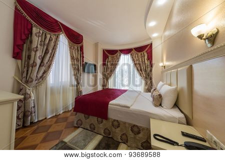 ADLER, RUSSIA - JULY 22, 2014: Interior of a hotel room with drapes and high bed in Shine House hotel