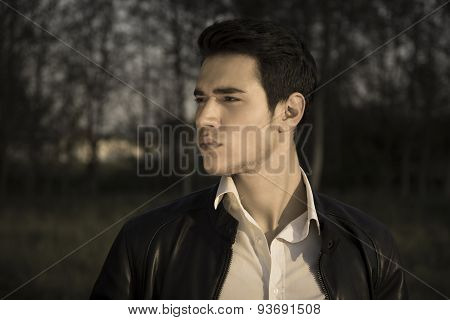 Handsome young man at countryside at night, in field