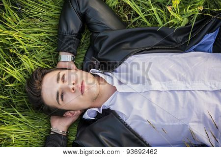 Good looking, fit male model relaxing lying on the grass