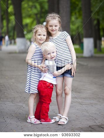 Blonde Little boy and two older cousins sisters, meeting in the summer park