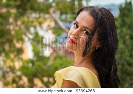 Brunette in a yellow dress on a balcony overlooking the villa and the sea.