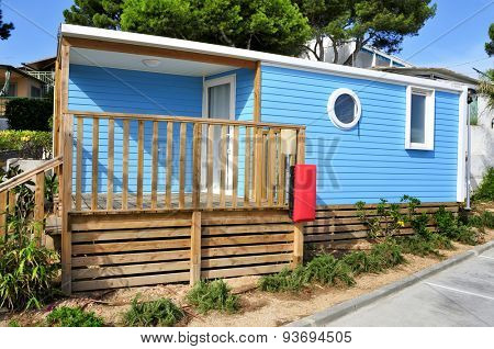 a nice blue mobile home with a wooden veranda in a campsite