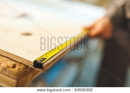 Worker measures wooden deck with tape measure with background blurred and selective focus on digits