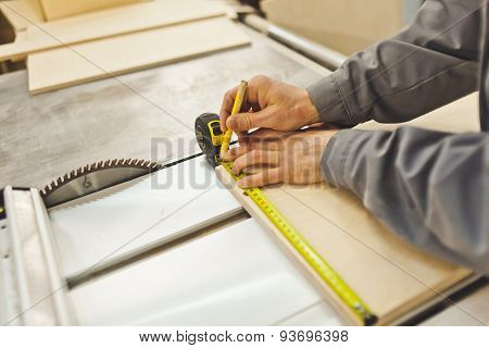 Carpenter with tape measure make marks on product with pencil near saw on workbench