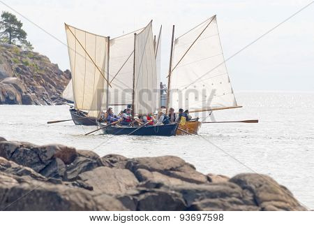 Group Of Small, Old Sailing Ships Vlose To The Rocks