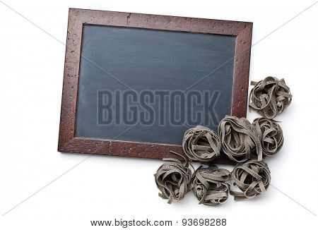black tagliatelle pasta and chalkboard on white background