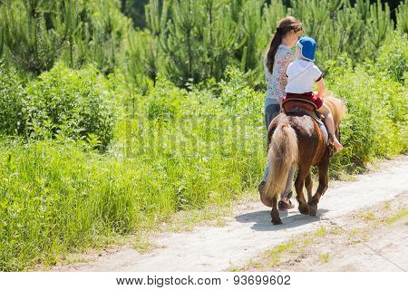 Boy riding on a pony,