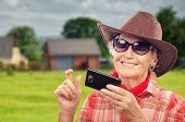 stock photo of cowgirl  - Old cowgirl surfing internet on smartphone in ranch - JPG