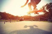 image of skateboard  - skateboarder legs riding skateboard at skatepark - JPG