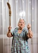 image of broom  - Old angry woman threatening with a broom at home - JPG