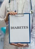 stock photo of diabetes symptoms  - Doctor holds blue clipboard with diabetes diagnosis - JPG
