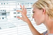 pic of peeping tom  - Curious blonde woman looking through venetian blind on a sunny day - JPG