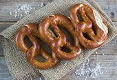 picture of pretzels  - Fresh pretzels with sea salt on wooden table - JPG