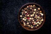foto of peppercorns  - Peppercorns in a wooden bowl on a dark background - JPG