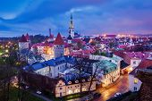 stock photo of olaf  - Aerial view of Tallinn Medieval Old Town illuminated in evening with dramatic sky - JPG