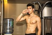 stock photo of dispenser  - Attractive athletic shirtless young man drinking water from dispenser in gym while looking at camera - JPG