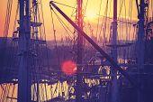 stock photo of mast  - Vintage toned sunrise over harbor sailing boats masts lens flare effect - JPG