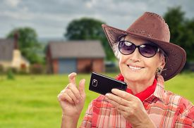 stock photo of cowgirls  - Old cowgirl surfing internet on smartphone in ranch - JPG