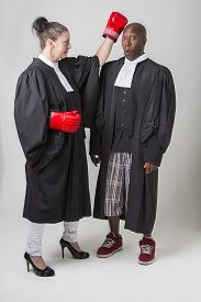 stock photo of toga  - woman punching a man on the head both wearing canadian lawyers toga - JPG