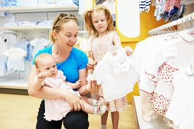 stock photo of apparel  - woman choosing children apparel with little baby and child girl on hands in clothing shop supermarket - JPG