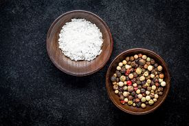 picture of peppercorns  - peppercorns and sea salt in a wooden bowl on a dark background - JPG