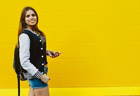 picture of rap-girl  - Happy young girl listening music  in headphones over yellowwall - JPG