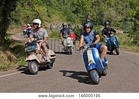 CESENA, ITALY - JUNE 26: group of bikers riding vintage italian scooters Vespa on the hills during the scooter rally