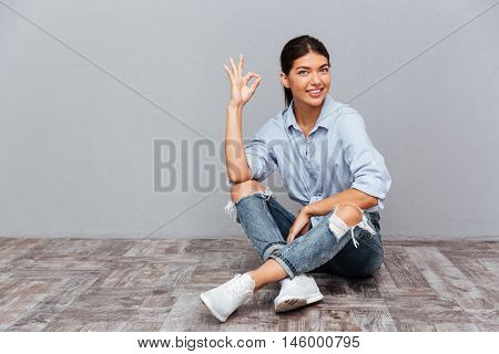 Portrait of a smiling young girl sitting on the floor and showing okay gesture isolated on a gray background