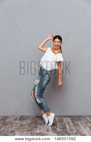 Beautiful cheerful smiling brunette girl standing on her tiptoes isolated on a gray background