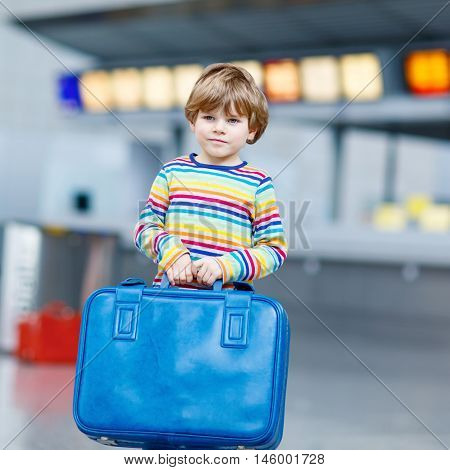 Cute little kid boy with blue suitcase on international airport. Happy child wating for flight and going on vacations.