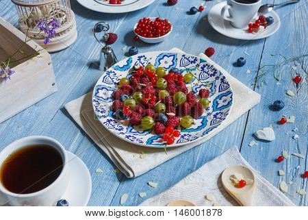 Sweet berries dessert - red currant, gooseberry, raspberry and bluberries. Healthy and natural food, diet nutrition. Beautiful dish served at blue rustic wooden table on white porcelain plate