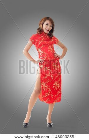 Smiling Chinese woman dress traditional cheongsam at New Year, studio shot isolated.